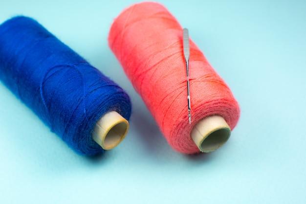 Niebieskie I Czerwone Szpule Nici Z Igłą, Z Bliska Premium Zdjęcia