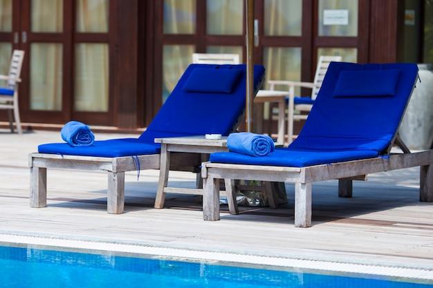 Niebieskie ręczniki na leżakach w pobliżu basenu w tropikalnym kurorcie Premium Zdjęcia