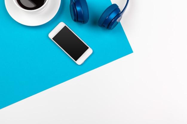 Niebieskie słuchawki na niebieskim i białym Premium Zdjęcia