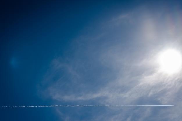 Niebieskiego nieba tło z promieniami słońca i samolotem wlec krzyżować niebo. Premium Zdjęcia