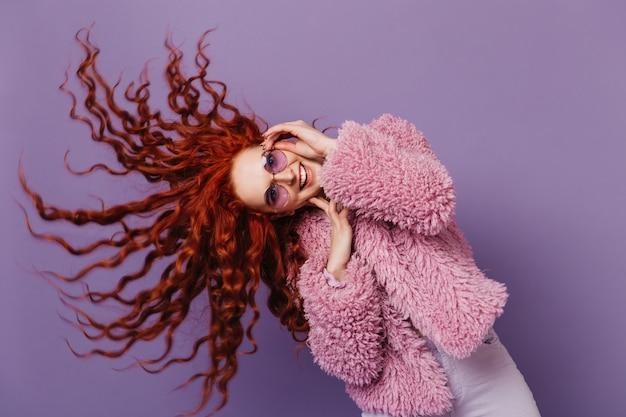 Niebieskooka Kobieta W Liliowych Okularach Tańczy I Bawi Się Włosami. Obraz Dziewczyny W Różowym Płaszczu Na Odizolowanej Przestrzeni. Darmowe Zdjęcia
