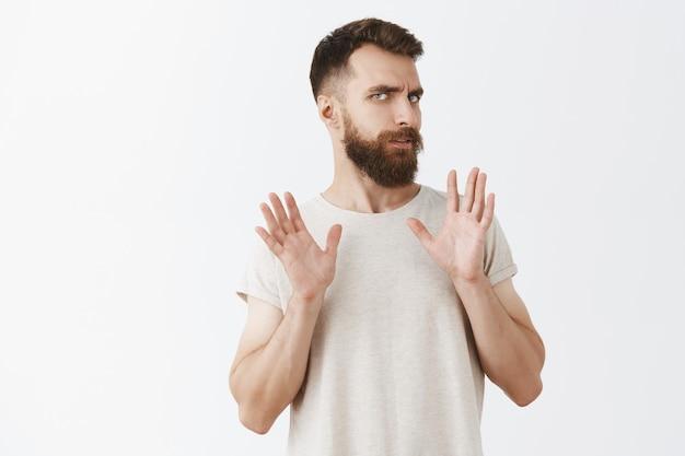 Niechętny I Zaniepokojony Brodaty Mężczyzna Pozuje Pod Białą ścianą Darmowe Zdjęcia