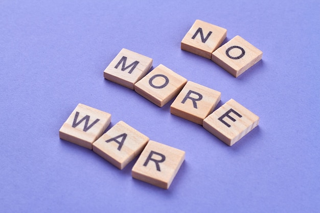 Niedopuszczalność Przemocy I Wojny. Slogan No More War Napisany Literami Na Drewnianych Kostkach. Na Białym Tle Na Niebieskim Tle. Premium Zdjęcia