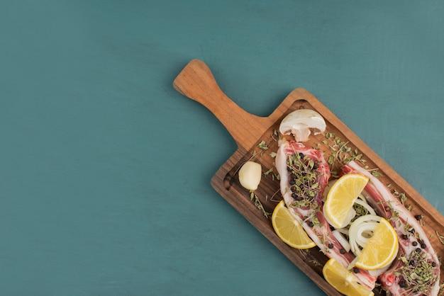 Niegotowane Kawałki Mięsa Na Desce Z Plasterkami Cytryny. Darmowe Zdjęcia