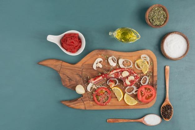 Niegotowany Kawałek Mięsa Z Warzywami, Olejem I Przyprawami Na Niebieskim Stole. Darmowe Zdjęcia
