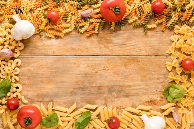 Niegotowany makaron z pomidorami; liście czosnku i bazylii ułożone na teksturowanej powierzchni Darmowe Zdjęcia