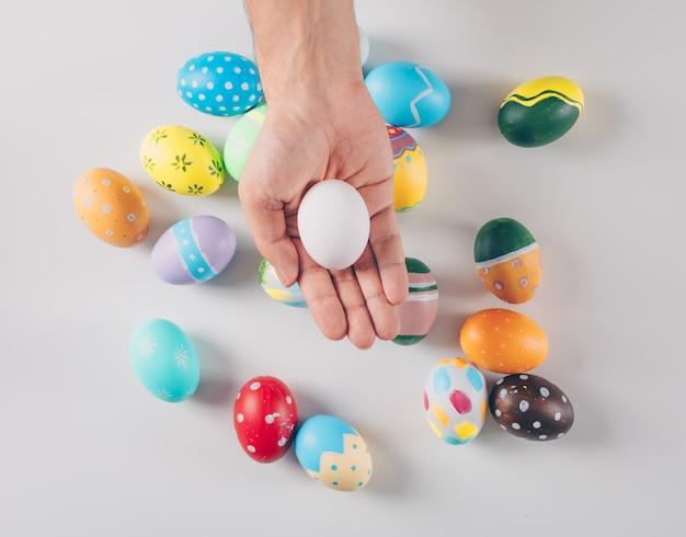 Niektóre Easter Jajka Z Mężczyzna Trzyma Jeden Białego Jajko Na Białym Tle, Odgórny Widok. Darmowe Zdjęcia
