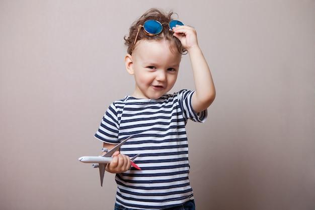 Niemowlę, Dziecko Z Zabawkowym Samolotem W Dłoniach I Okularami Przeciwsłonecznymi. Premium Zdjęcia