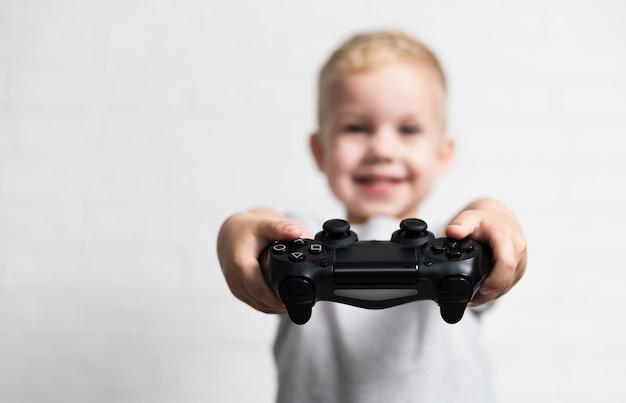 Nieostry mały chłopiec trzyma kontrolera Darmowe Zdjęcia