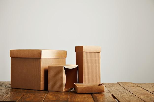 Nieoznakowane Podobne Pudełka O Różnych Kształtach I Rozmiarach Na Nierównym Drewnianym Stole Na Białym Tle Darmowe Zdjęcia