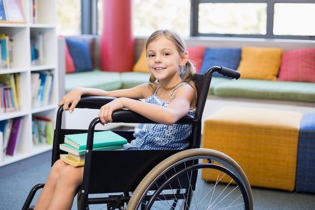 Niepełnosprawna Szkolna Dziewczyna Z Książkami W Bibliotece Premium Zdjęcia