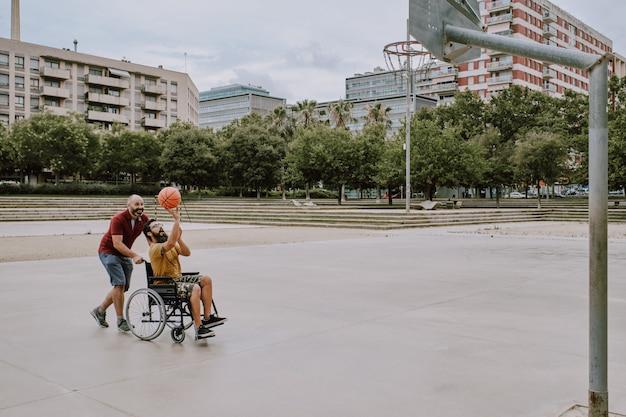 Niepełnosprawny mężczyzna na wózku inwalidzkim gra z przyjacielem w koszyku Premium Zdjęcia