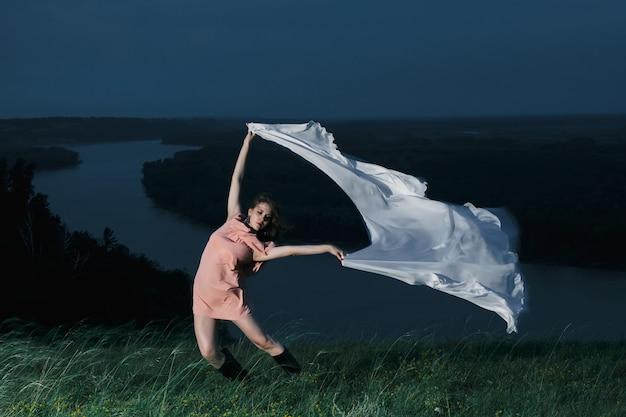 Niesamowita Dziewczyna Tańcząca W Różowej Sukience Z Dużym Białym Szalem W Nocy Premium Zdjęcia