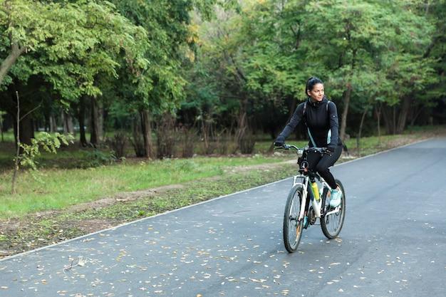 Niesamowita ładna Kobieta Spaceru Na Rowerze W Parku Na świeżym Powietrzu. Premium Zdjęcia