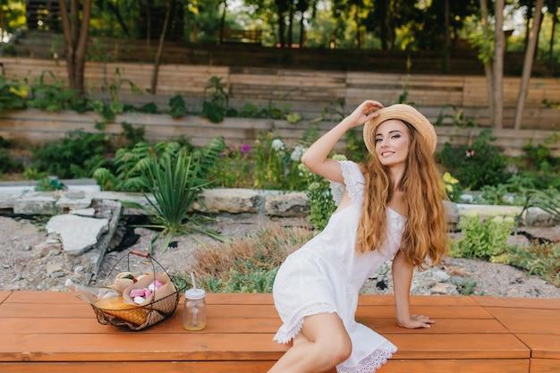 Niesamowita Młoda Kobieta Z Jasnobrązowymi Włosami, Pozowanie, Dotykając Rocznika Kapelusz I Uśmiechając Się. Cudowna Dziewczyna W Modnej Białej Sukni Siedzi Przy Kwietniku Z Koszem Piknikowym. Darmowe Zdjęcia