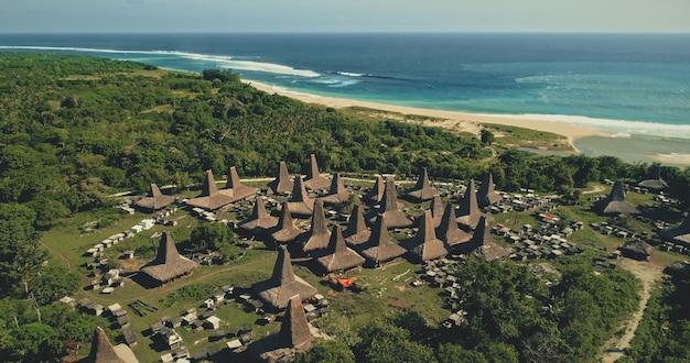 Niesamowita Nadmorska Tradycyjna Wioska Z Unikalnie Zaprojektowanymi Dachami Mieści Widok Z Lotu Ptaka. Atrakcją Turystyczną Indonezji W Zielonej Dolinie Z Drzewami Zwrotnikowymi W Pobliżu Zatoki Oceanicznej. Filmowy Widok Z Drona Premium Zdjęcia