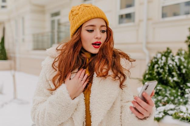 Niesamowita Rudowłosa Kobieta Z Telefonem Stojącym Na Ulicy. śliczna Imbirowa Dama W Płaszczu I Kapeluszu, Trzymając Smartfon. Darmowe Zdjęcia