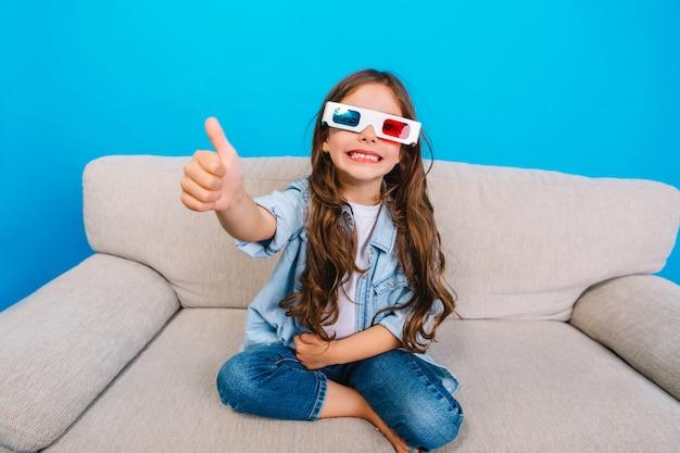 Niesamowita Szczęśliwa Mała Dziewczynka W Okularach 3d Z Długimi Włosami Brunetka Uśmiecha Się Do Kamery Na Kanapie Na Białym Tle Na Niebieskim Tle. Okazywanie Prawdziwych Pozytywnych Emocji, Szczęśliwego Dzieciństwa Modnego Dzieciaka Darmowe Zdjęcia