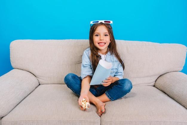 Niesamowita Szczęśliwa Mała Dziewczynka Z Długimi Brunetkami Uśmiecha Się Do Kamery Na Kanapie Na Białym Tle Na Niebieskim Tle. Noszenie Okularów 3d Na Głowie, Przygotowanie Do Oglądania Filmu Z Popcornem, Wyrażanie Pozytywności Darmowe Zdjęcia