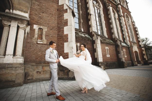 Niesamowita uśmiechnięta para ślubna. ładna panna młoda i stylowy pan młody w pobliżu kościoła Premium Zdjęcia