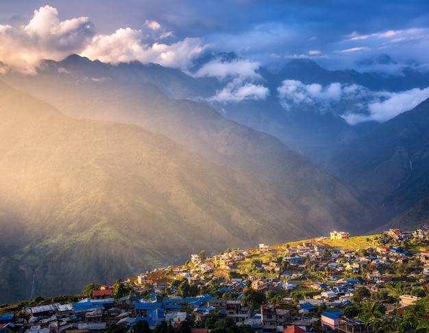 Niesamowita Wioska Na Wzgórzu Oświetlona Promieniem Słońca O Zachodzie Słońca Premium Zdjęcia