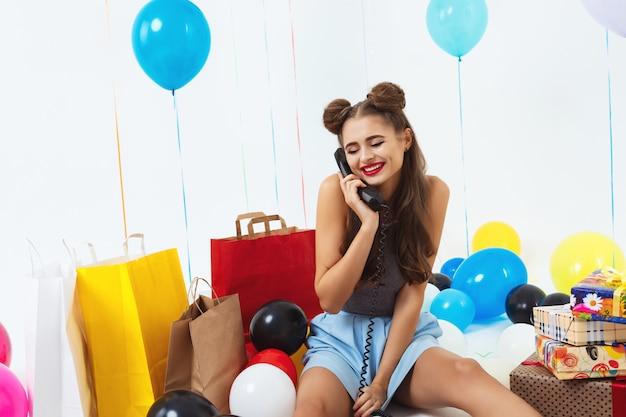 Nieśmiała I ładna Dziewczyna Siedzi Z Prezentami Urodzinowymi I Otrzymuje życzenia Darmowe Zdjęcia