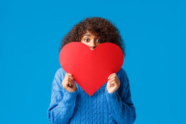 Nieśmiała I Zarumieniona śliczna Dziewczyna Przestraszyła Się, że Przyznaje Się Do Dziewczyny, Którą Ją Kocha, Trzymając Duży Czerwony Słuch I Ukrywając Twarz, Zerkając Na Aparat Z Nerwowym Przestraszonym Spojrzeniem, Stojąc Na Niebiesko Niezdecydowanym Premium Zdjęcia