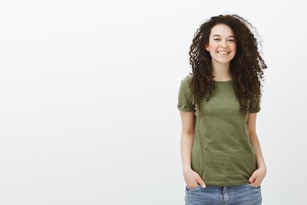 Nieśmiała śliczna Uczennica Z Kręconymi Włosami W Ciemnozielonej Koszulce Darmowe Zdjęcia