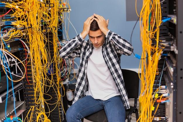 Niespokojny inżynier sieci siedzi na serwerowni Darmowe Zdjęcia