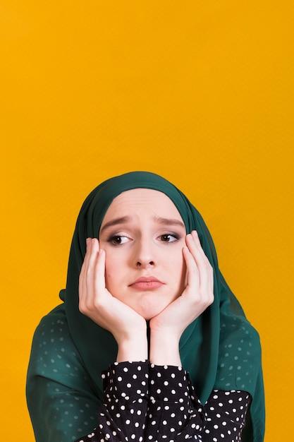 Nieszczęśliwa młoda islamska kobieta patrzeje daleko od przed żółtym tłem Darmowe Zdjęcia