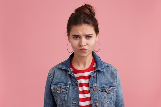 Nieszczęśliwa, Przygnębiona śliczna Młoda Kobieta W Dżinsowej Kurtce W Paski T-shirt, Marszczy Brwi I Patrząc Na Kamery, Odizolowane Na Różowej ścianie. Darmowe Zdjęcia