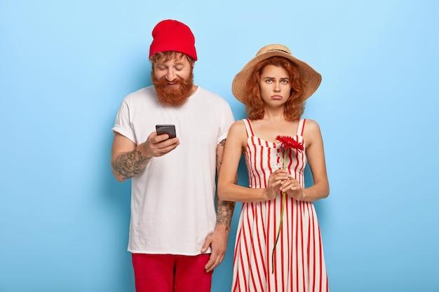 Nieszczęśliwa Ruda Kobieta Nudzi Się, Podczas Gdy Chłopak Używa Telefonu Komórkowego Darmowe Zdjęcia
