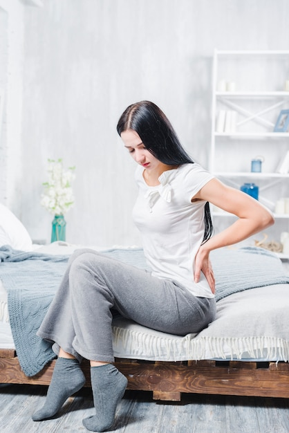 Nieszczęśliwy Kobiety Obsiadanie Na Drewnianym łóżkowym Cierpieniu Od Bólu W Plecy Premium Zdjęcia