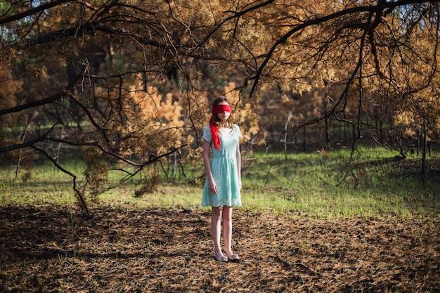 Niewolnictwo. Bardzo śliczna Młoda Dziewczyna Z Opaską Czerwoną Wstążką. Wygląd Lalki. Kobieta Z Brązowymi Włosami W Turkusowej Sukni Na Charakter. Długie Włosy. Naturalne światło. Model Stwarzające Na Charakter. Porwanie Premium Zdjęcia