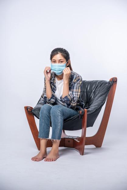 Niewygodna Kobieta Siedząca Na Krześle I Nosząca Maskę Darmowe Zdjęcia