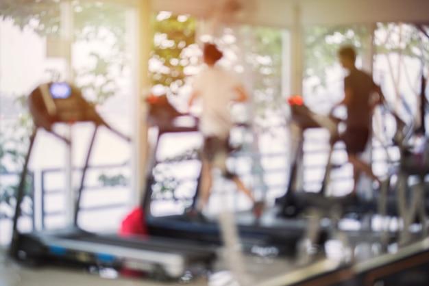 Niewyraźne centrum fitness z urządzeniami do ćwiczeń wysiłkowych i treningiem siłowym. liczby ludzi biegających na bieżniach w siłowni. Premium Zdjęcia