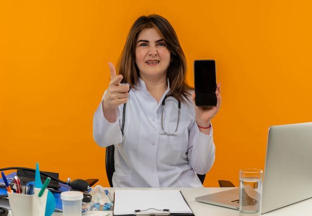 Niezadowolona Kobieta W średnim Wieku Ubrana W Szlafrok Medyczny Ze Stetoskopem Siedząca Przy Biurku Na Laptopie Z Narzędziami Medycznymi Trzymająca Telefon I Pokazująca Gest Na Pomarańczowej ścianie Darmowe Zdjęcia