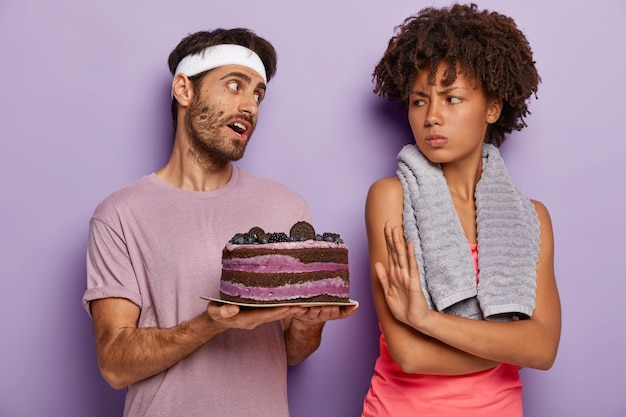 Niezadowolona Kobieta Wykonuje Gest Odmowy, Prosi O Nie Sugerowanie Jedzenia Słodyczy, Patrzy Ze Złością Na Męża Trzymającego Smaczne Ciasto Darmowe Zdjęcia