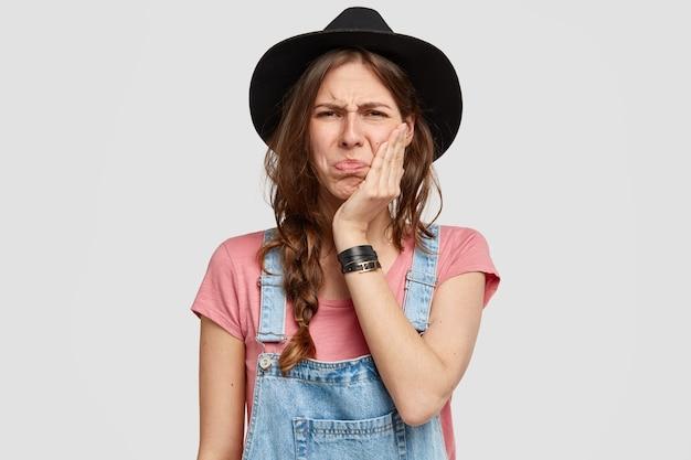 Niezadowolona Młoda Kobieta Robotnik Rolniczy Ma żałosny Wyraz Twarzy, Dotyka Ręką Policzka, Ubrana W Dżinsowy Kombinezon I Modny Kapelusz Darmowe Zdjęcia