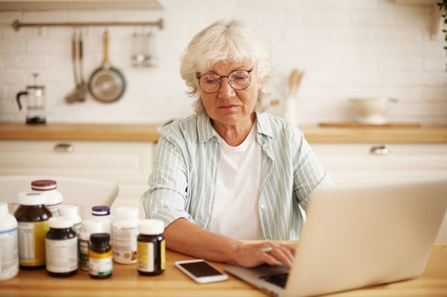 Niezadowolona Starsza Emerytowana Europejka W Okrągłych Okularach Siedzi W Kuchni, Patrzy Z Pogardą Na Butelki Z Suplementem Diety, Pisze Gniewną Negatywną Recenzję Na Stronie Internetowej Za Pomocą Laptopa Darmowe Zdjęcia