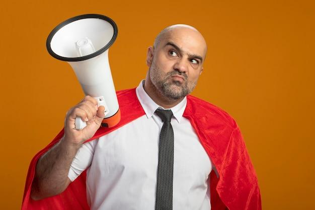 Niezadowolony Biznesmen Super Bohater W Czerwonej Pelerynie Trzymając Megafon Patrząc Na Bok Stojąc Nad Pomarańczową ścianą Darmowe Zdjęcia