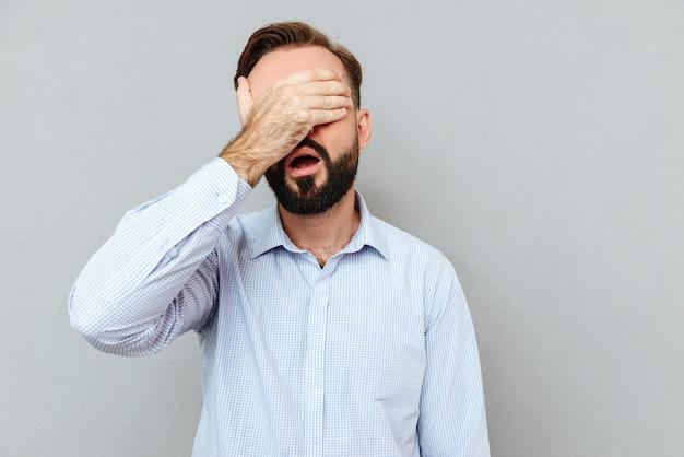Niezadowolony Brodaty Mężczyzna W Biznesowych Ubraniach Zakrywających Oczy Darmowe Zdjęcia