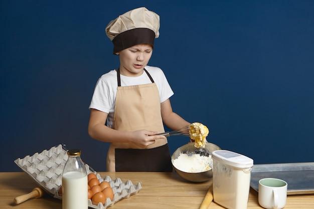 Niezadowolony Kaukaski Mały Chłopiec W Mundurze Szefa Kuchni, Stojący Przy Stole W Kuchni I Marszczący Brwi O Zdegustowanym Zdenerwowanym Wyrazie Darmowe Zdjęcia