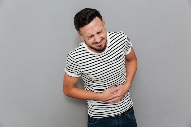 Niezadowolony Młody Człowiek Z Bolesnymi Uczuciami, Trzymając Brzuch Darmowe Zdjęcia