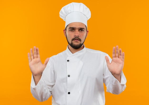 Niezadowolony Młody Kucharz W Mundurze Szefa Kuchni Pokazuje Puste Ręce Na Pomarańczowej Przestrzeni Darmowe Zdjęcia