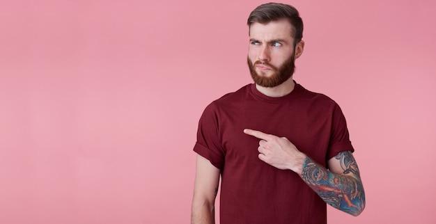 Niezadowolony Młody Przystojny Rudy Brodaty Mężczyzna W Czerwonej Koszuli, Chce Zwrócić Twoją Uwagę Na Skopiowanie Miejsca Po Lewej Stronie, Wskazując Palcami I Pytająco Patrzy Na Niego, Stoi Na Różowym Tle. Darmowe Zdjęcia