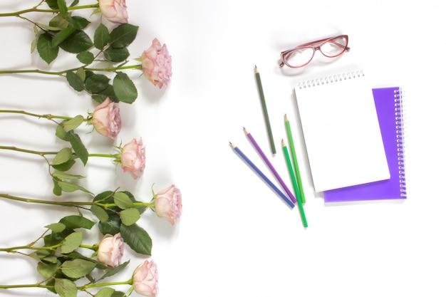 Niezależny Artysta Kobieta Obszar Roboczy. Szkicownik, Kolorowe Ołówki, Okulary I Pastelowe Różowe Róże Na Pulpicie Premium Zdjęcia