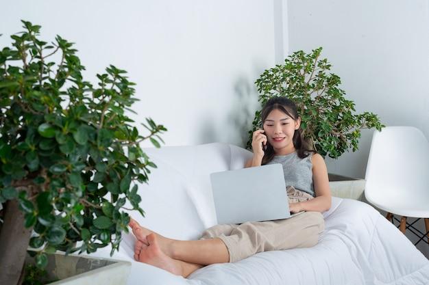 Niezależny, Pracujący W Domu - Młoda Kobieta Korzysta Z Telefonu Podczas Pracy W Salonie. Darmowe Zdjęcia