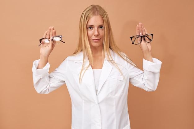 Niezdecydowana Piękna Młoda Klientka Trzymająca Okulary Z Wątpliwym Wyrazem Twarzy Darmowe Zdjęcia