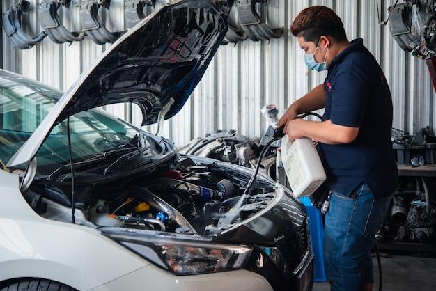 Niezidentyfikowany Mechanik Samochodowy Lub Serwisant Czyszczący Silnik Samochodu Po Sprawdzeniu Silnika Samochodu Premium Zdjęcia